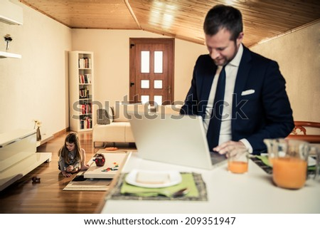 Young father working at home during breakfast while his little girl is playing on the floor - stock photo