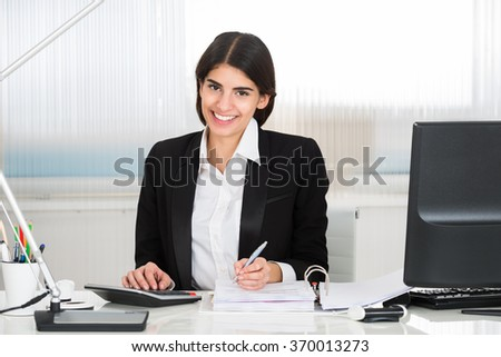 Young female accountant calculating finance with calculator at desk in office - stock photo
