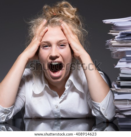 Young female accountant having a lot of paperwork - stock photo