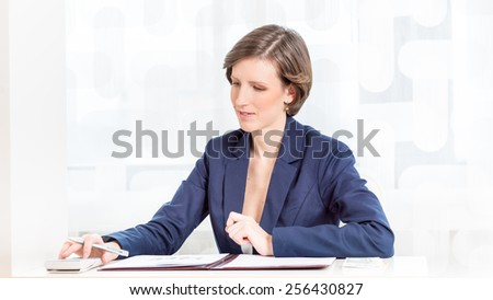 Young female accountant working at her desk with documents and calculator. - stock photo
