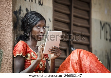 Young Female African Student Posing With Her Tablet in College - stock photo
