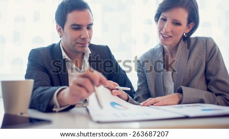Young female and male business executives looking at business papers or report and cheerfully discussing their success, with a faded retro look. - stock photo