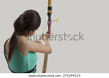 Young female archer aiming arrow against gray background - stock photo