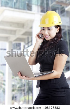 Young female architect checking her plan on the laptop while talking on the phone - stock photo