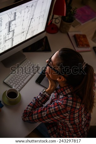 Young female architect working at home.She works  late into the night.View from above. - stock photo