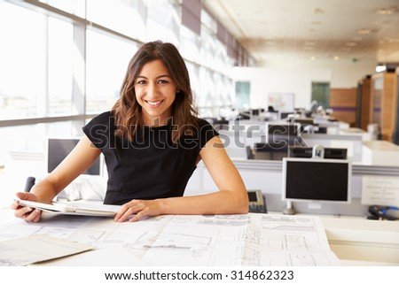 Young female architect working with computer and blueprints - stock photo