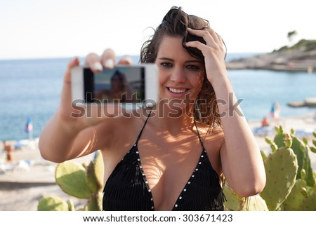 Young Female At The Seashore Taking Selfie Using Smart Phone - stock photo