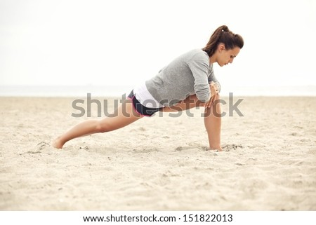 Young female athlete doing stretching exercise on the beach for fitness and a healthy lifestyle. - stock photo