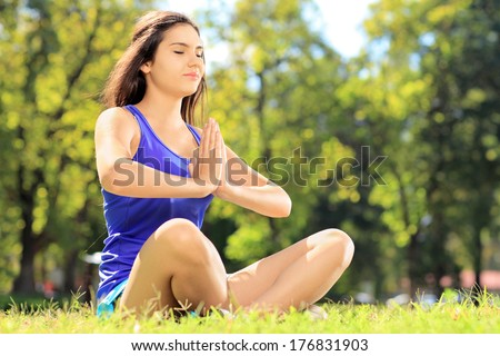 Young female athlete in sportswear doing yoga exercise seated on a grass in a park - stock photo