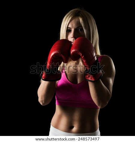 Young female athlete on a boxing training - stock photo