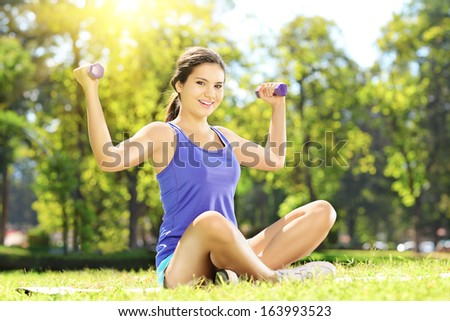 Young female athlete seated on a green grass exercising with dumbbells in a park - stock photo