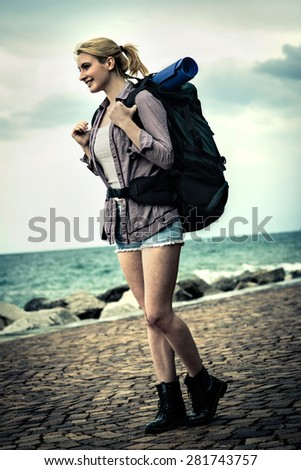 Young female backpacker by the sea - stock photo