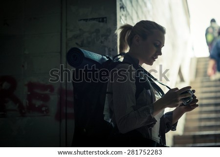 Young female backpacker in subway using camera - stock photo