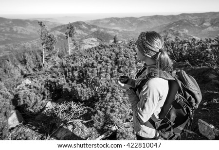 Young female backpacker resting on mountain peak with cup of tea/coffee, enjoying view of valley below. black and white - stock photo