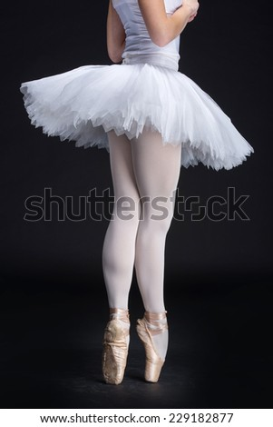 Young female ballerina is standing on toes, on the black background. - stock photo
