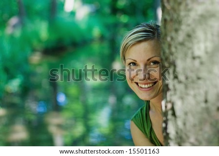 young female behind a tree smiling - stock photo