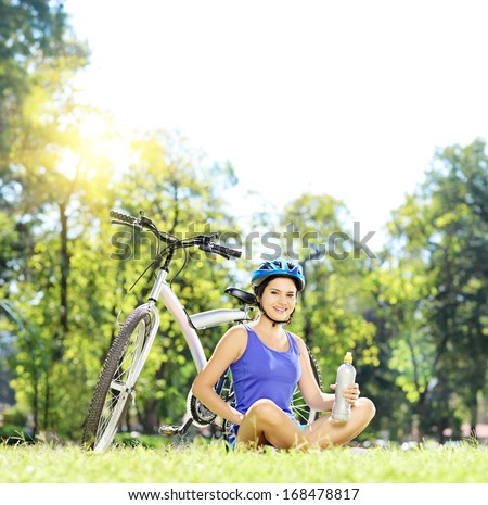 Young female biker sitting on a green grass next to a mountain bike and drinking water, shot with a tilt and shift lens - stock photo