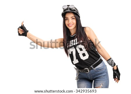 Young female biker with helmet and goggles hitchhiking with her thumb isolated on white background - stock photo