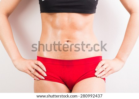 young  female body in fitness sports clothing, with sweat. Athletic woman - stock photo