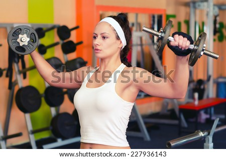 Young female bodybuilder lifting weights in the gym. - stock photo