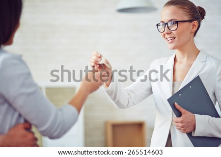Young female broker giving her client key from new flat - stock photo