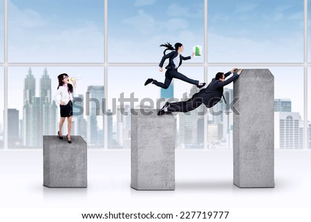 Young female business manager giving command to her team on the business graph - stock photo