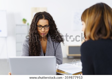 Young female business team in a meeting with two businesswomen sitting together discussing information on a laptop computer with a serious expression - stock photo