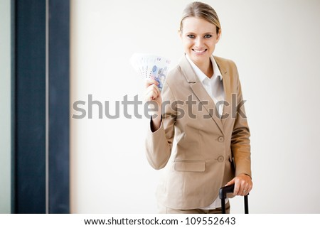 young female business traveller holding South African money - stock photo