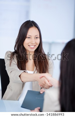 Young female candidate shaking hands with businesswoman at office desk - stock photo