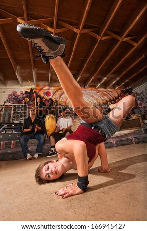 Young female capoeira performer kicking from the ground - stock photo
