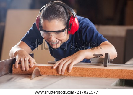 Young female carpenter in safety equipment cutting wood with tablesaw in workshop - stock photo