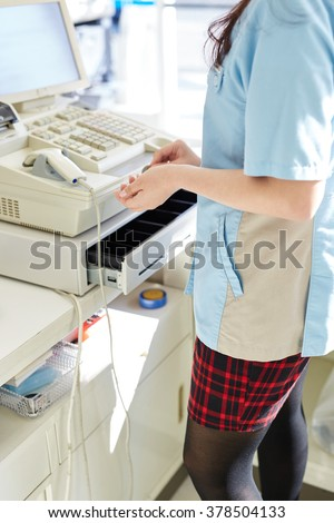 Young female cashier helping a customer pay - stock photo
