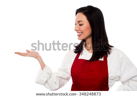 Young female chef presenting something - stock photo