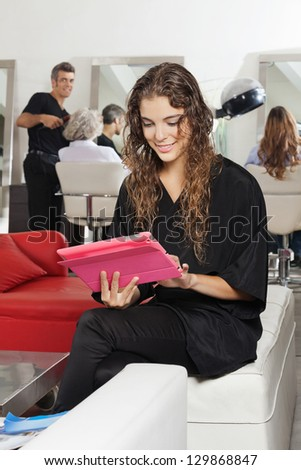 Young female client using digital tablet with hairdresser and women in the background in salon - stock photo