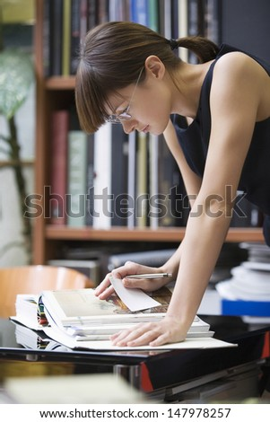 Young female college student researching in library - stock photo
