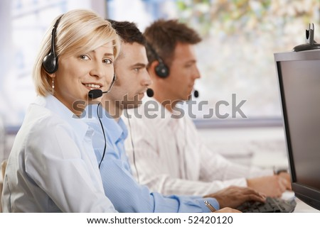 Young female customer service operator talking on headset, looking at camera, smiling. - stock photo