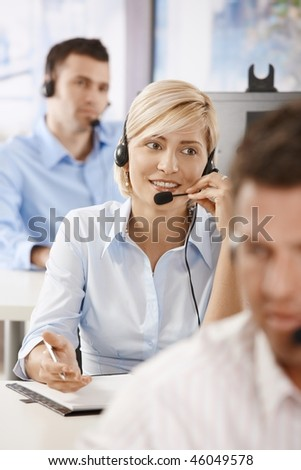Young female customer service operator talking on headset, smiling. - stock photo