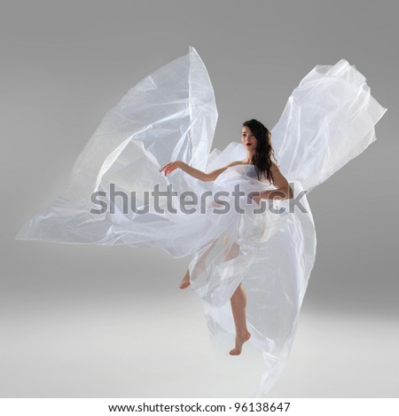 Young female dancer posing over gray background - stock photo