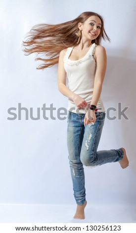 Young female dancing, fluttering on the wind hair, over white background - stock photo