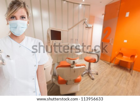 Young female dentist holding a syringe - stock photo