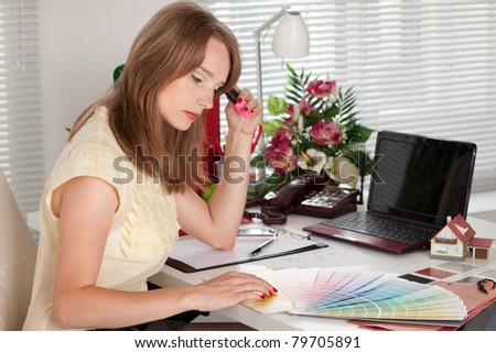 Young female designer of interior sits on the workplace at the office. - stock photo
