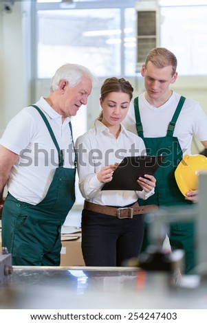 Young female director of warehouse and her two employees - stock photo