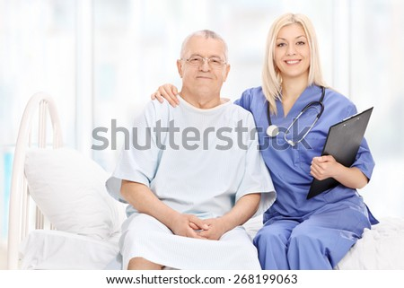 Young female doctor and a mature patient posing seated on a hospital bed - stock photo