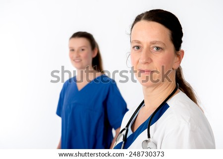 young female doctor and nurse in front of white background - stock photo