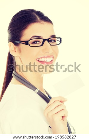 Young female doctor holding business card - stock photo