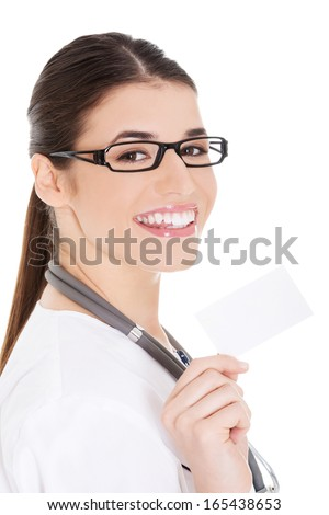 Young female doctor holding business card. Isolated on white.  - stock photo