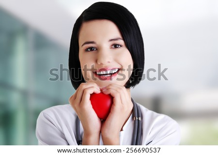 Young female doctor holding heart model - stock photo