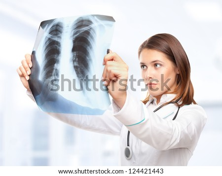 Young female doctor looking at the x-ray picture of lungs in hospital - stock photo