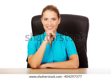 Young female doctor or nurse sitting behind the desk - stock photo