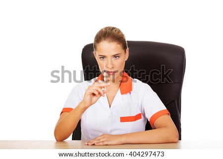 Young female doctor or nurse sitting behind the desk and holding syringe - stock photo